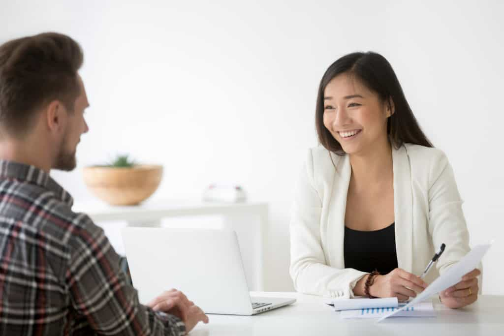 Friendly asian hr smiling talking to candidate at job interview