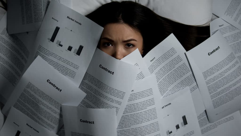 woman covered by piles of documents
