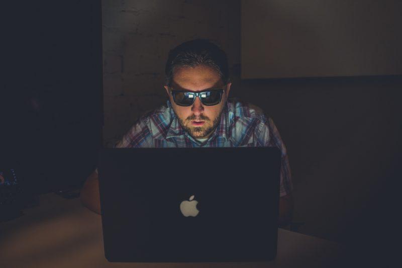 man using laptop to ensure mobile security